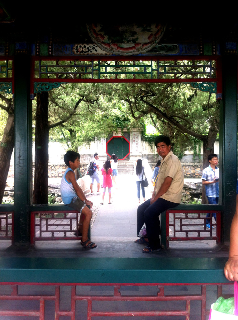 A father and son sitting in the long corridor at the Summer Palace.
